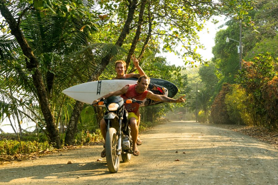 surfers doubling on motorcycle shakas good times travel